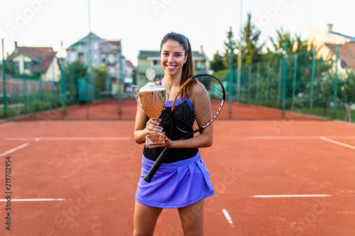 Portrait of beautiful teenage tennis player holding big trophy and smiling.