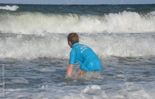 Fotografia, Obraz  Kind beim Baden im Meer - Ostsee - hohe Wellen - Wellengang