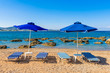 Sun loungers with umbrellas on sandy Kolymbia beach. Rhodes island, Greece