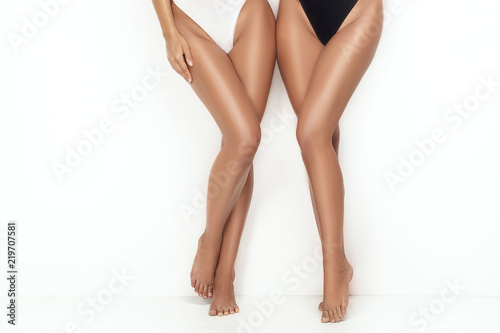 Obraz na plátne Tanned sexy legs of two girls.