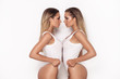 canvas print picture Sensual twins women posing on white background.