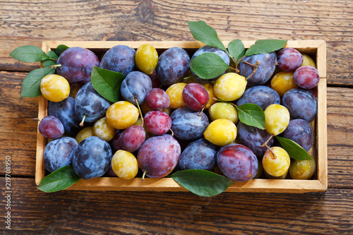colorful plums with leaves in a wooden box