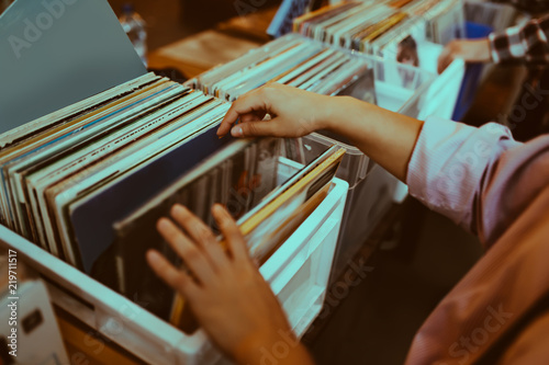 Poster de jardin Magasin de musique Woman is choosing a vinyl record in a musical store