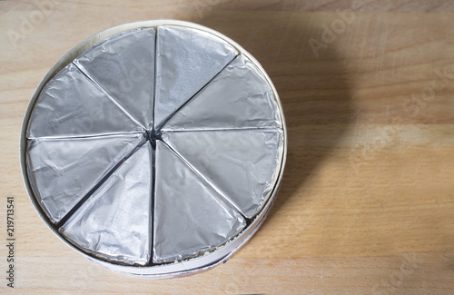 Round Cardboard Box With Melted Cheese In Aluminium Foil On Wooden