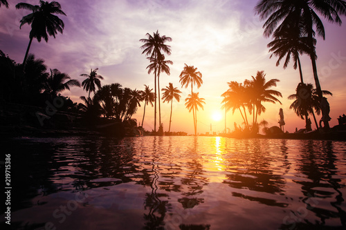 Twilight on a tropical beach with silhouettes of palm trees reflections in water in surreal color.