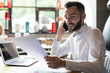Portrait of handsome bearded businessman wearing white shirt speaking by phone and reading documents while working at table in office or cafe