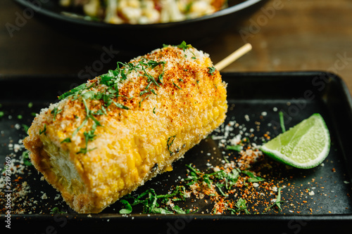 Mexican style grilled corn topping with cheese and chili powder served with sliced lime in black plate.