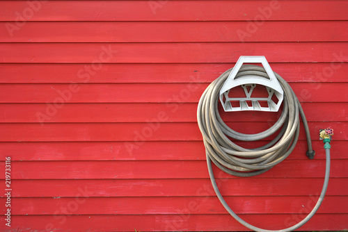 Fotografie, Obraz  background of garden hose reel mounted on the wall
