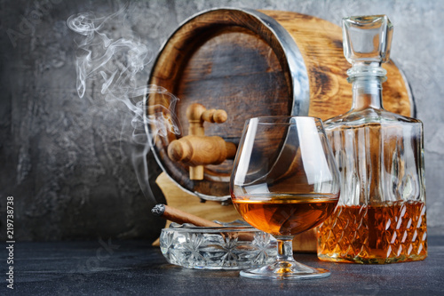 .Strong alcoholic drink cognac in sniffer glass with smoking cigar in ashtray, crystal decanter and vintage wooden barrel