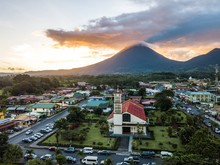 Beautiful Aerial View Of The Fortuna Town, Church, Park And The Arenal Volcano At Sunset In Costa Rica