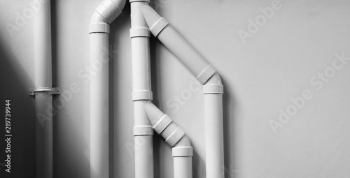 Fotografie, Obraz white plastic pipe at white cement wall with shadow.
