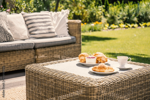Fotografia  Beige color wicker table and settee on a porch during sunny afternoon in the garden