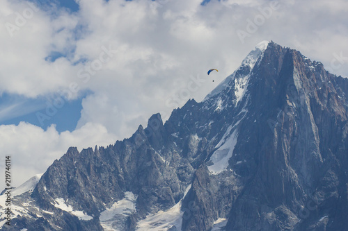 Paragliding at snow mountains over ski resort. Rock Mountains in winter.