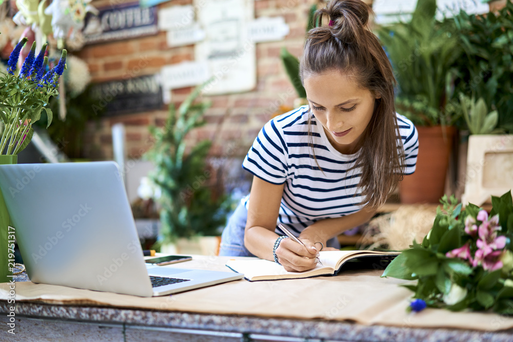 Fototapeta Portrait of florist writin in notebook while leaning against counter with laptop