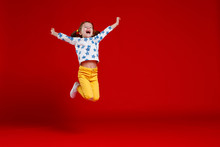 Funny Child Girl Jump In Glasses On Colored Background