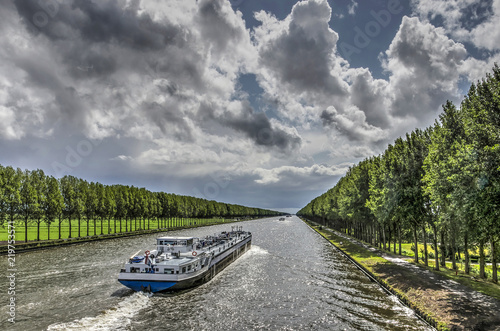 Inland barge on the long straight tree-lined Amsterdam-Rhine canal just south of Fototapete