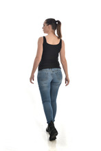 Full Length Portrait Of Brunette Girl Wearing Black Single And Jeans. Standing Pose With Back To The Camera. Isolated On White Studio Background.