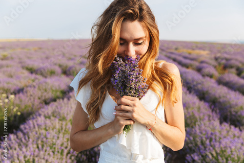 Fototapeta Photo of caucasian young woman in dress holding bouquet of flowers, while walking outdoor through lavender field in summer obraz