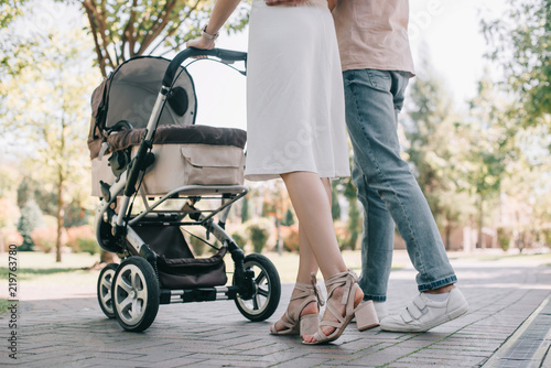Photo cropped image of parents walking with baby carriage in park