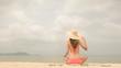 Woman in pink bikini with sun hat sitting at the beach in summer