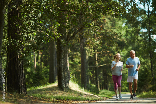 Foto Healthy active senior couple in sportswear running among green trees on sunny da
