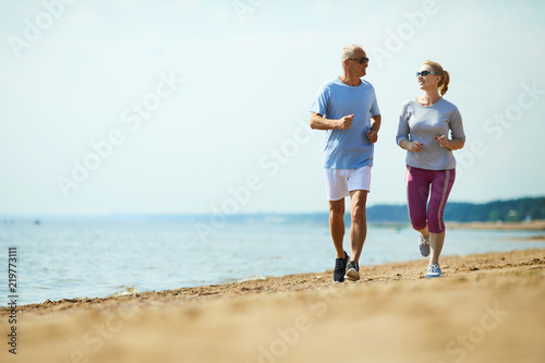 Poster de jardin Jogging Active senior man and woman running down sandy beach with waterside on background