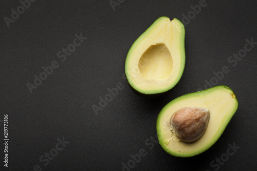 fresh green avocado isolated on dark background. top view