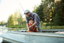 Father Teaching His Happy Son To Fishing, He Helps Him To Hold A Rod, They Sitting On The Boat