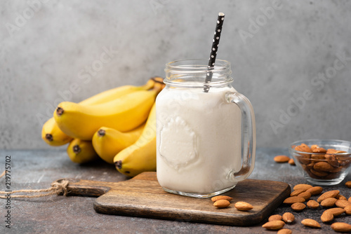 Banana protein smoothie in drinking glass on wooden serving board
