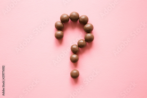 Fototapeta  Question mark created from chocolate balls on the pastel pink table