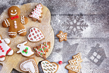 Christmas Cookies Of Various Shapes In Sugar Glaze On A Cutting Board On A Brown Wooden Table Sprinkled With Flour, Flat Lay, Copy Space. Christmas Composition With Gingerbread Men, Fir-trees, Rabbit.