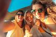 Leinwanddruck Bild - Three female friends enjoying traveling in the car. Sitting in rear seat and and making selfie.