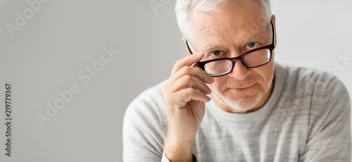 Fotografiet  old age, problem and people concept - close up of senior man in glasses thinking
