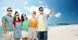 travel, summer holidays and tourism concept - group of happy smiling friends in sunglasses hugging pointing finger to something over tropical beach background in french polynesia