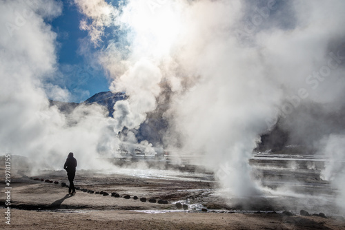 Fotomural El Tatio geysers in Chile, Silhouette of a woman walking among the steams and fu