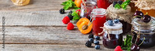 Photo  Assortment of seasonal berries and fruits jams in jars
