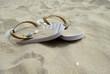 Gros plan d' une paire de tongs rayées sur une plage en partie recouvertes par le sable et quelques coquillages
