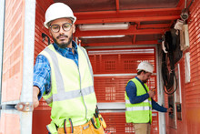 Waist Up Portrait Of Middle-Eastern Construction Worker Wearing Hardhat Closing Doors Entering Elevator With Crew, Copy Space