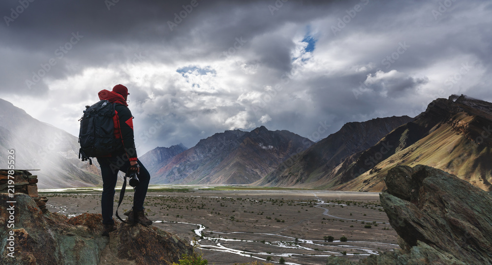 Fototapety, obrazy: a man with backpack holding camera standing on cliff with mountains view and sunlight through cloud. Travel lifestyle, adventure and success concept