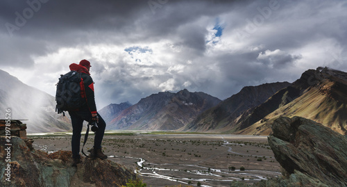 Fototapeta a man with backpack holding camera standing on cliff with mountains view and sunlight through cloud