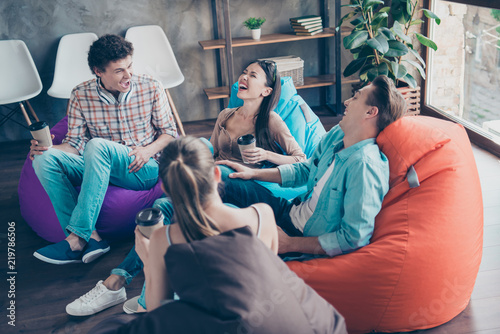 Fotografia  Rejoice and cheerful trandy youths sitting in a loft style room with coffee in h