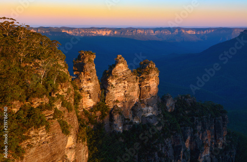Fotografie, Tablou Orange glow of sunset on the peaks of the Three Sisters landmark in the Blue Mou