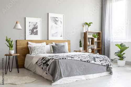 Fotografía  Patterned blanket on wooden bed in grey bedroom interior with plants and posters