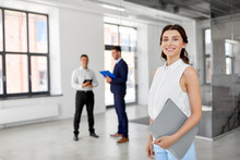 Real Estate Business, Sale And People Concept - Happy Smiling Realtor Or Businesswoman With Folder And Customers At New Office Room