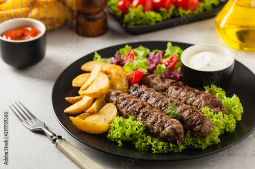 Traditional cevapcici served with baked potatoes. Stone background.