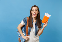 Portrait Of Young Overjoyed Woman Student In Glasses With Backpack Hold Passport, Boarding Pass Tickets Isolated On Blue Background. Education In University College Abroad. Air Travel Flight Concept.