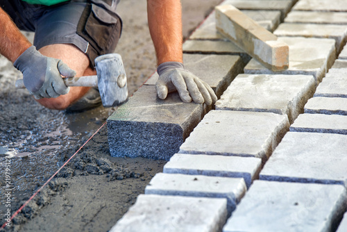 A workman's gloved hands use a hammer to place stone pavers. Worker creating pavement using cobblestone blocks and granite stones.