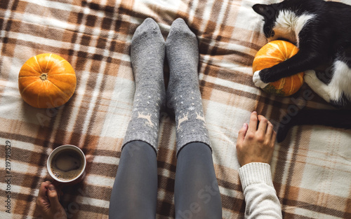 Foto op Canvas Herfst Women's hands and feet in sweater and woolen cozy gray socks holding cup of hot coffee, sitting on plaid with kitten, pumpkin, candles and leaves. Concept winter comfort, morning drinking.