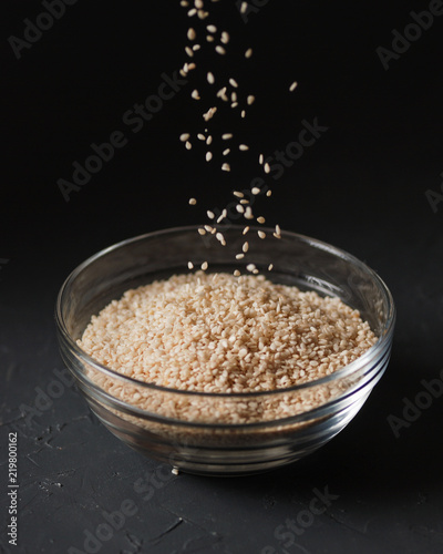 Sesame seeds in a transparent glass bowl on a dark gray background. Close up