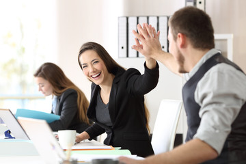 Two happy coworkers celebrating success at office